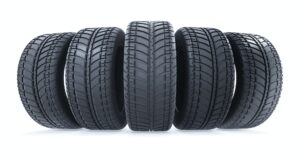 Car tires in row on white background. New black wheel tyres for